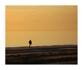 Man in a coat running along the beach on a warm evening.